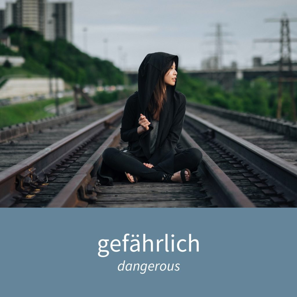 "Image showing a woman sitting on train tracks and the caption ""gefährlich - dangerous"""