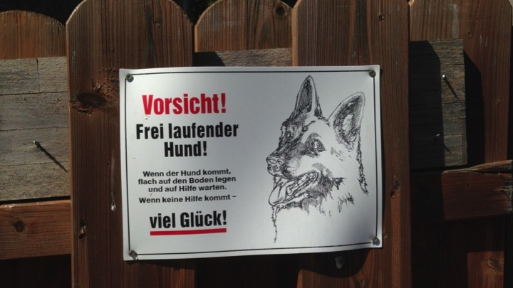 "Image of a sign on a fence showing a dog and the text ""Vorsicht! Frei laufender Hund!"""
